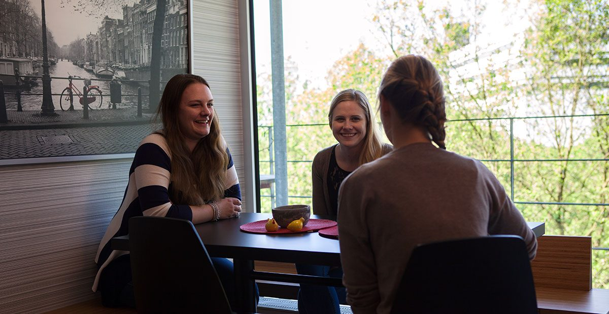 three students having a conversation in a dormtitory sitting next to a table
