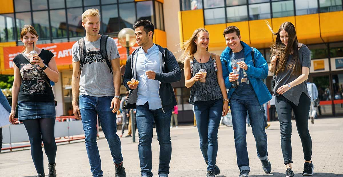 a group of students stroll on campus, enjoying food and beverages
