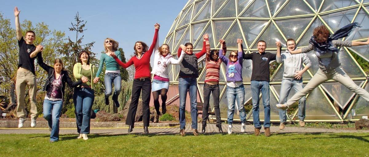 Leistungsbilanz 2013 Foto:14 lachende Studierende springen auf einem Rasen in die Luft.