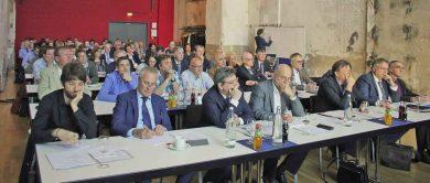 Symposium - An Tischen sitzende Teilnehmenden des Symposiums in der Jahrhunderthalle in Bochum.