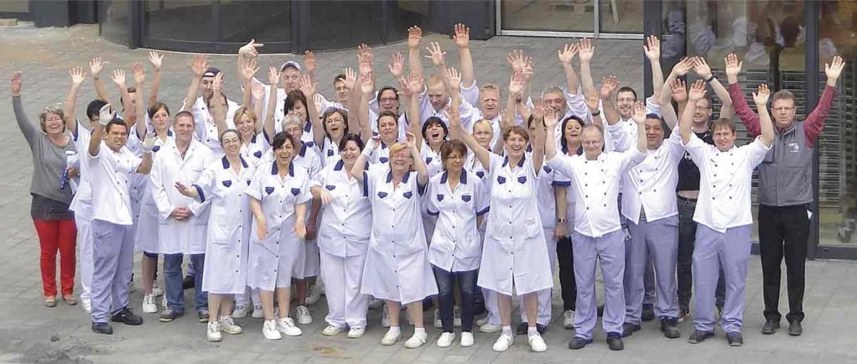 Leistungsbilanz 2014 - 35 Mitarbeitende halten lachend die Arme in die Höhe.