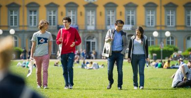 Studierendenwerk Bonn, Viele Studierenden sitzen auf dem Rasen der Universität Bonn. 4 Studierende kommen auf die Kamera zu und unterhalten sich