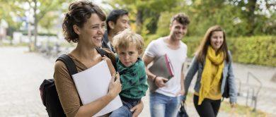 Mutter mit Kleinkind auf dem Arm geht mit einer Mappe, Rucksack auf dem Rücken einen Weg entlang. Hinter ihr laufen 3 Studierende. 2 Männer und eine Frau.