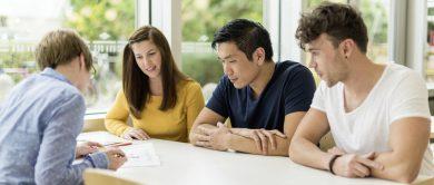 4 Studierende sitzen arbeitend an einem Tisch