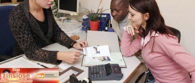 1 Mitarbeiterin berät 2 Studierende an ihrem Schreibtisch.