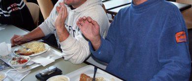 Tablets mit gefüllten Tellern und 2 Männer, die mit den Händen eine geste zur der Anerkennung des guten Geschmacks machen.