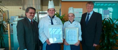 Zwei Auszubildende Köche in der Mitte des Bildes mit Urkunden in der Hand , an den Seiten stehen der Abteilungsleiter und der Geschäftsführer