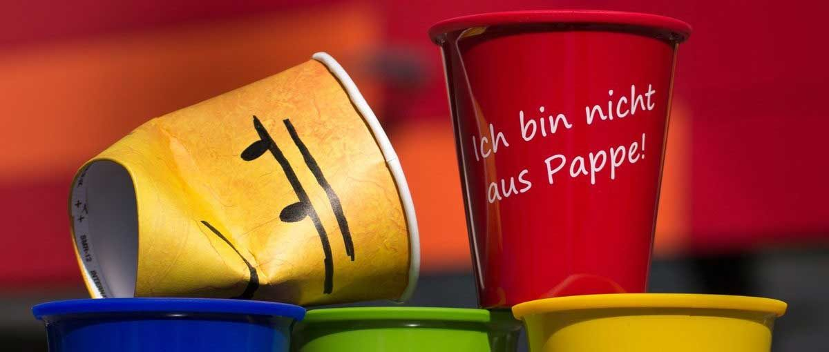 Gelber zerknautschter Pappbecher mit Zeichnung grimmiges Gesicht und der schöne rote MensaCup aus Kunststoff