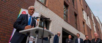 Der Oberbürgermeister steht an einem Stehpult und spricht in ein Mikrofon. Im Hintergrund stehen mehrere Zuhörer, darunter auch der Geschäftsführer des Studierendenwerks Bonn.