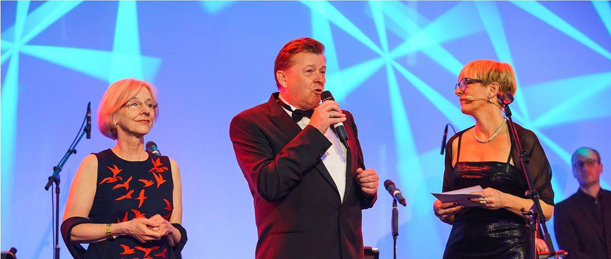 Auf einer Bühne spricht Herr Lüken in ein Mikrofon. Er steht in Abendgarderobe in der Mitte zwischen Frau X und Frau Z.