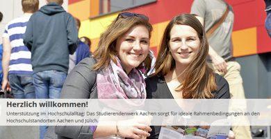 Zwei weibliche Studierende stehen vor einem rot gelben Gebäude, schauen lächelnd in die Kamera und zeigen ein aufgeklapptes Faltblatt.