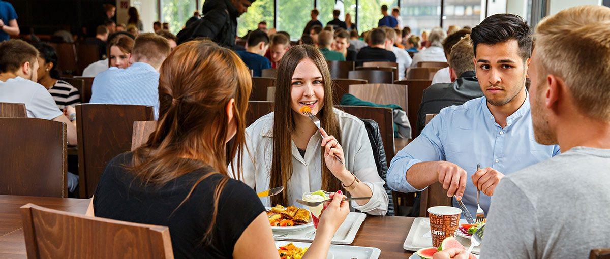 studierende essen in einer modernen mensa und unterhalten sich angeregt