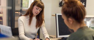 eine studentin sucht beratung im studierendenwerk und sitzt im büro einer mitarbeiterin zum gespräch.