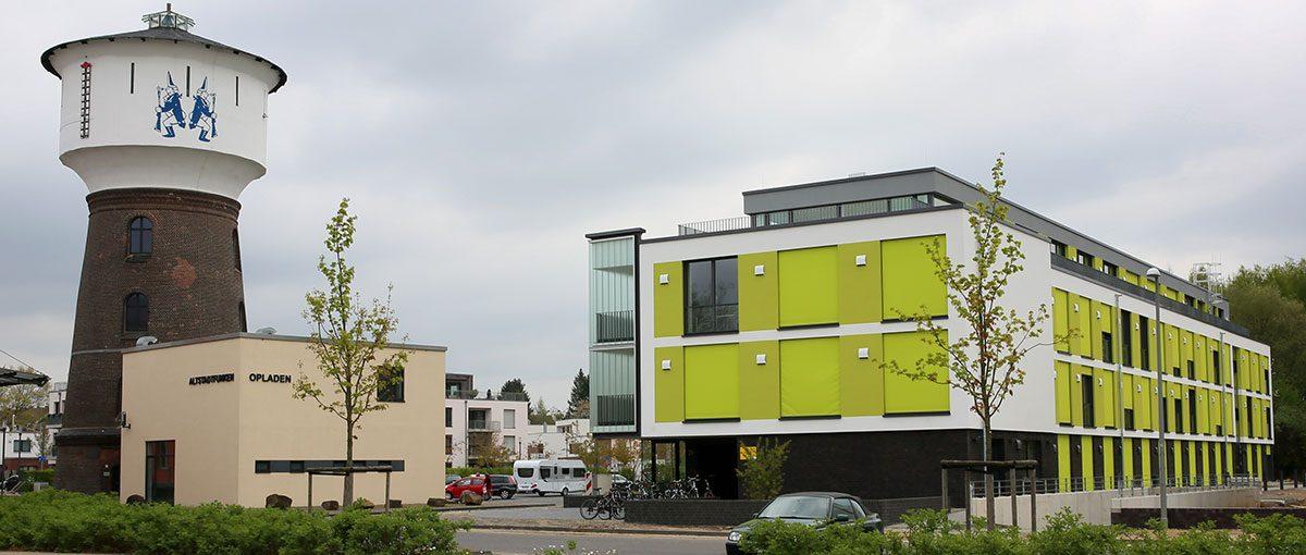 es ist ein studierendenwohnheim neben einem turm und einem kleinen häusschen zu sehen. das wohnheim hat auffallend grüne fensterläden.