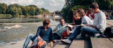 fünf studierende sitzen auf eienr treppe. im hintergrund ein schönes brückenpanorama.