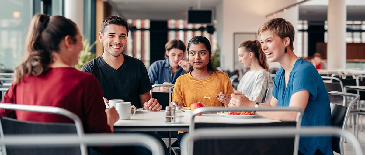 vier studierende sitzen am tisch eienr mensa. sie essen und unterhalten sich angeregt.