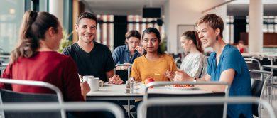 vier studierende sitzen am tisch einer mensa. sie essen und unterhalten sich angeregt.