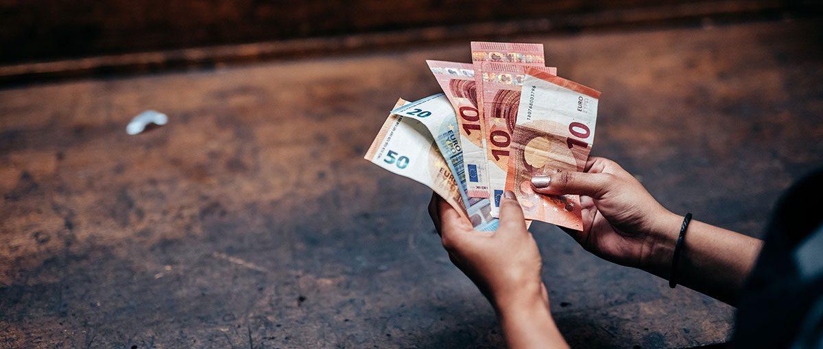 es sind mehrere geldscheine in der hand eines studenten zu sehen. die szene soll das bafög repräsentieren, sprich, die studienfinanzierung