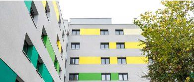 Die Fassade der sanierten Wohnanlage wird durch Farbgebungen aufgelockert.