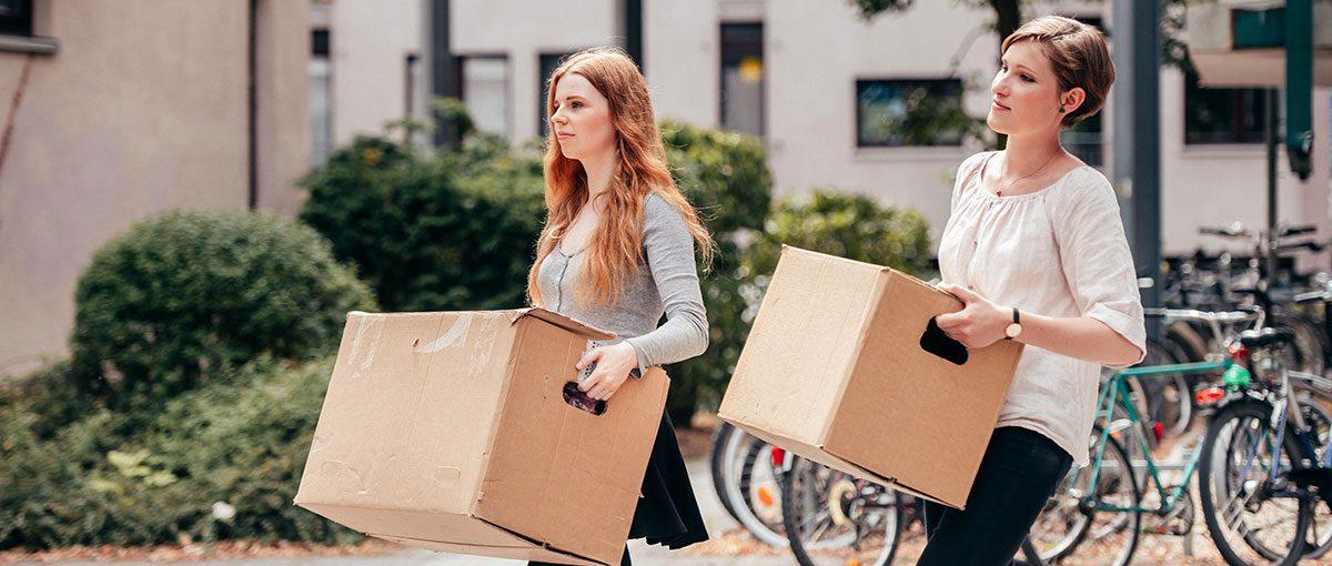 Zwei Studentinnen tragen Umzugkartons zu ihrer neuen WG in einer Studierendenwohnanlage.
