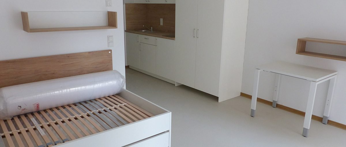 Zu sehen sind Küchenzeile, Bett und Tisch eines modernen Apartments.