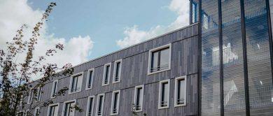 Graue Außenfassade mit weiß umrandeten Fenstern der neuen Bochumer Wohnanlage Siepenfeld.